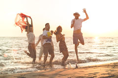 Group of happy young people dancing at the beach on beautiful summer sunset.  Royalty Free Stock Photo