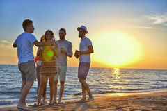 Group of happy young people dancing at the beach on beautiful summer sunset.  Stock Photo
