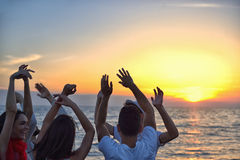Group of happy young people dancing at the beach on beautiful summer sunset.  Royalty Free Stock Photos