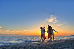 Group of happy young people dancing at the beach on beautiful summer sunset.  Stock Image