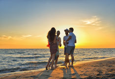 Group of happy young people dancing at the beach on beautiful summer sunset.  Stock Images