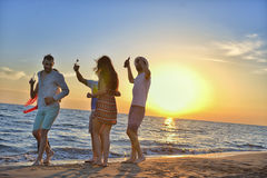 Group of happy young people dancing at the beach on beautiful summer sunset.  Royalty Free Stock Image