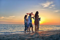 Group of happy young people dancing at the beach on beautiful summer sunset Royalty Free Stock Photo