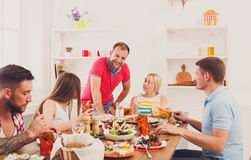 Group of happy young people at dinner table, friends party Royalty Free Stock Photos