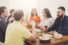 Group of happy young people at dinner table, friends party Stock Photography