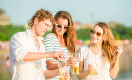 Group of happy young people drinking beer on the Royalty Free Stock Photos