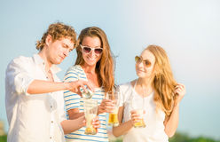 Group of happy young people drinking beer on the Royalty Free Stock Photo