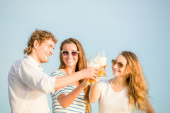 Group of happy young people drinking beer on the Stock Photo