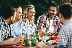 Group of happy people eating food outdoors Stock Images