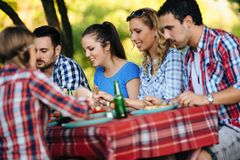 Group of happy people eating food outdoors Stock Image