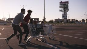 Group of happy young people having fun on shopping trolleys. Multiethnic young people racing on shopping cart. Beautiful stock video