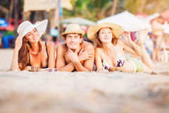 Group of happy young people lying on wite beach. Group of happy young people in bathing suits lying on the beach with wite sand and having fun in sunset sun Stock Images
