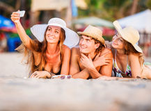 Group of happy young people lying on wite beach Stock Images