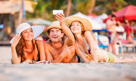 Group of happy young people lying on wite beach. Group of happy young people in bathing suits lying on the beach with wite sand and having fun in sunset sun and Stock Photos