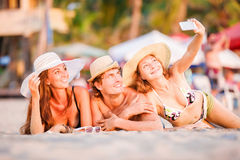 Group of happy young people lying on wite beach. Group of happy young people in bathing suits lying on the beach with wite sand and having fun in sunset sun and Royalty Free Stock Photography