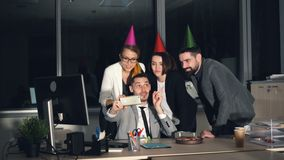 Group of young people is making online video call skyping from office wearing party hats talking, waving hand, sending stock footage