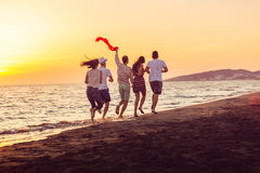Group of happy young people is running on background of sunset beach and sea Royalty Free Stock Image