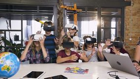 Group of happy young pupils of elementary school using virtual reality headsets during computer coding class. Slow motion stock video footage