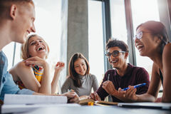 Group of happy young students in library. Multiethnic young people sitting at table and having fun while studying together for exams. Group of happy young Stock Photos