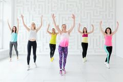 Group of happy young women with coach having a cardio workout in the fitness studio royalty free stock photo