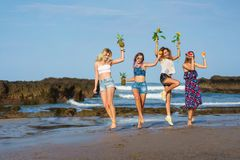 Group of happy young women with fruits and sunflowers. On beach royalty free stock photos