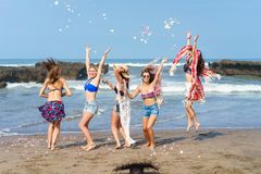 Group of happy young women having fun and throwing up petals. On beach royalty free stock photography