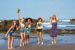 Group of happy young women holding various fruits. On beach stock photography