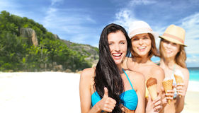 Group of happy young women with ice cream on beach Stock Images