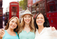 Group of happy young women over london city street. Summer holidays, people, travel, tourism and vacation concept - group of smiling young women over london city Royalty Free Stock Photo