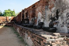 Group of headless Buddha statue in Wat Mahathat. A spectacular view from Wat Mahathat with stones, pillars, walls and pavement which is ruined by aggressor in Stock Photo