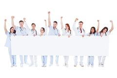 Group of healthcare personnel holding a banner. Large diverse group of healthcare personnel standing in a line holding a blank white banner with copyspace and Stock Photography