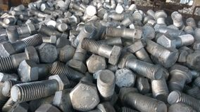 Group of Hex Bolts. A close up click of group of galvanized Hex bolts made up of strong steel metal alloy randomly placed in a metal bin royalty free stock image