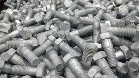Group of Hex Bolts. A close up click of group of galvanized Hex bolts made up of strong steel metal alloy randomly placed in a metal bin stock image