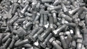 Group of Hex Bolts. A close up click of group of galvanized hex nuts made up of strong steel metal alloy randomly placed in a metal bin royalty free stock photo