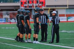 High School Football Players With Referees. A group of high school football players talking with the referees stock photo