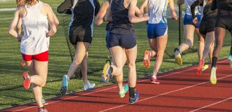 High school girls racing the mile. A group of high school girls are running away from the camera during a 1500 meter race on a red track Royalty Free Stock Photography