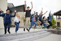 Group Of High School Students Jumping In Air Outside College Buildings stock photos