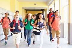 Group Of High School Students Running Along Corridor. Towards Camera Smiling Royalty Free Stock Images