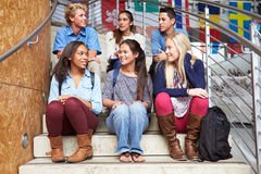 Group Of High School Students Sitting Outside Building Stock Images