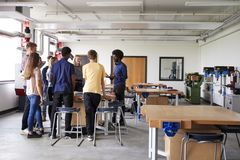 Group Of High School Students Standing Around Work Bench Listening To Teacher In Design And Technology Lesson royalty free stock photography