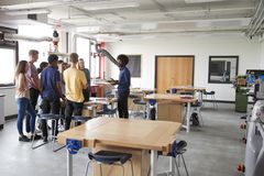Group Of High School Students Standing Around Work Bench Listening To Teacher In Design And Technology Lesson stock photography