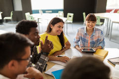 Group of high school students with tablet pc. Education, high school, people and technology concept - group of international students sitting at table with royalty free stock photography