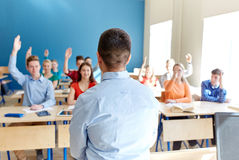Group of high school students and teacher. Education, high school, teaching, learning and people concept - group of happy students raising hands and teacher in Royalty Free Stock Images