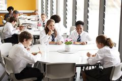 Group Of High School Students Wearing Uniform Sitting Around Table And Eating Lunch In Cafeteria royalty free stock photo