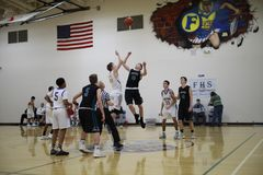 High School Basketball Game. A group of highschool students play basketball in a gym stock photography