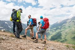 A group of hikers with backpacks and tracking sticks rest and stands in the mountains listening to their guide Royalty Free Stock Images