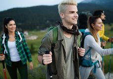 Group of hikers with backpacks and sticks walking on mountain. Friends making an excursion stock photography
