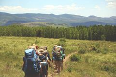 Group of Hikers with Backpacks Walking on Grassland Trail Royalty Free Stock Photos