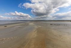 Group of hikers in the bay at low tide. Hike in the bay with a knowledgeable guide. Mont Saint-Michel , Normandy,. France stock photo