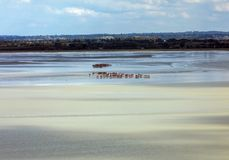 Group of hikers in the bay at low tide. Hike in the bay with a knowledgeable guide. Mont Saint-Michel , Normandy,. France stock photography
